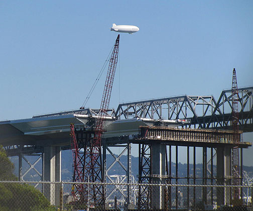 Dirigible over new and old Bay Bridge from Treasure Island