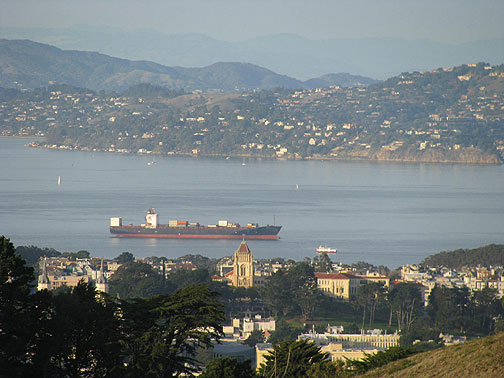Close-up from Twin Peaks northward, partially filled container ship entering bay, Tiburon in background.