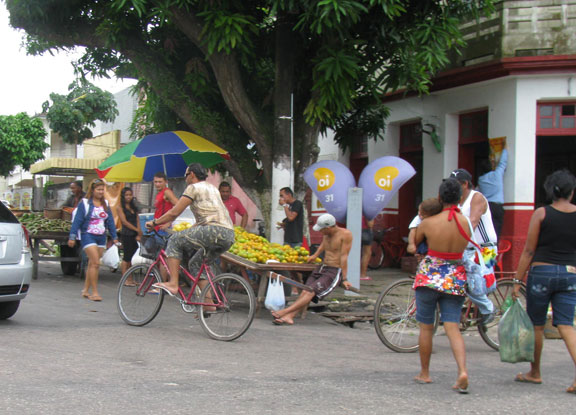 Bikes turn the corner in front of street vendor in Icoaraci.