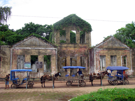 An elegant ruin at the dock in Cotijuba, horsedrawn taxis in front.