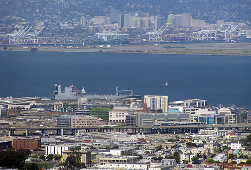 From Twin Peaks you can see two dominant industries that straddle the Bay: past the freeway the new office buildings make up UCSF Mission Bay, a biotech campus, and across the bay is the abandoned Alameda Naval Air Station with the many cranes that dominate the Port of Oakland and have been the linchpin of globalization.