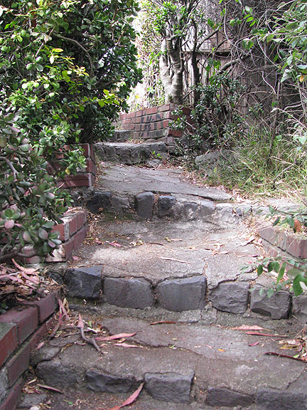 As you climb the stairs become more regular, and at the top you ascend a cement flight and emerge from behind a fence. This path is well hidden!