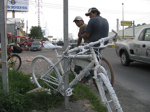 Two workers going home on bike pass a just-installed Ghost Bike.