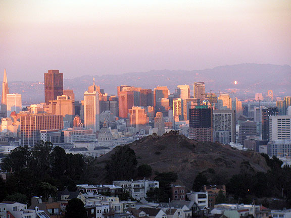 Sunset view from Tank Hill, sun lighting up windows in east bay hills, Corona Heights in foreground.