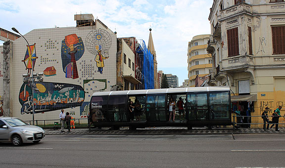 A BRT (Bus Rapid Transit) stop in downtown Curitiba, with a huge mosaic mural behind it.