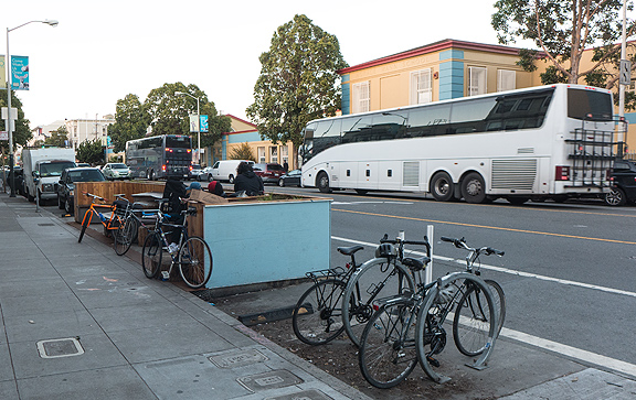The stark demographics of San Francisco show up as two luxury buses dedicated to shuttling tech workers from SF to their workplaces in Silicon Valley cruise by a bicycle-filled parklet in front of the collectively-run bakery Arizmendi.