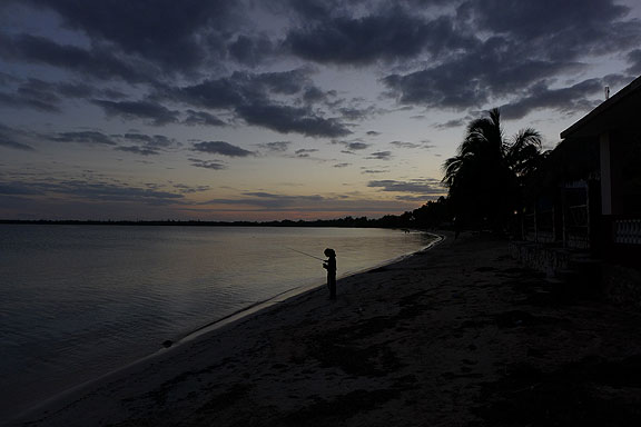 Young girl fishing at sunset, Bay of Pigs.